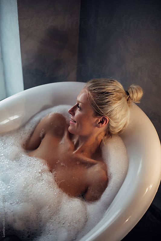 Blonde Woman Relaxing in the Bathtub  by Lumina for Stocksy United