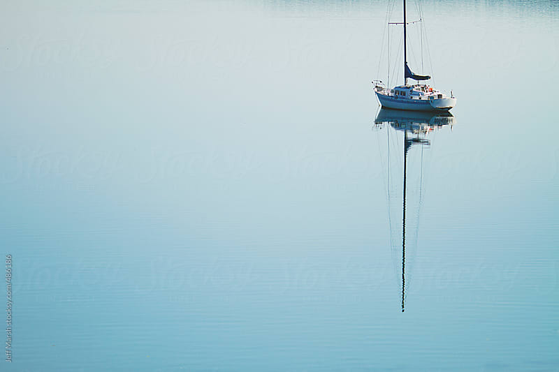 Sailboat on calm water by Jeff Marsh for Stocksy United