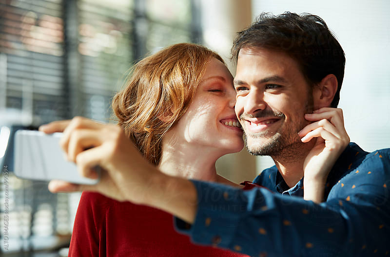 Happy Woman Kissing Man While Talking Selfie by ALTO IMAGES for Stocksy United