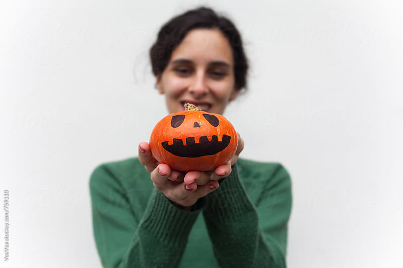 Woman in a green swetaer holding a small Halloween pumpkin  by Marija Mandic for Stocksy United