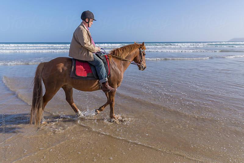 Profile of senior male riding horseback in shorebreak by Ben Ryan for Stocksy United