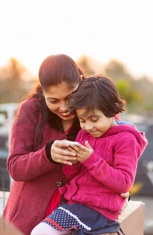 Mother and daughter browsing on mobile phone in a cheerful mood by Saptak Ganguly for Stocksy United