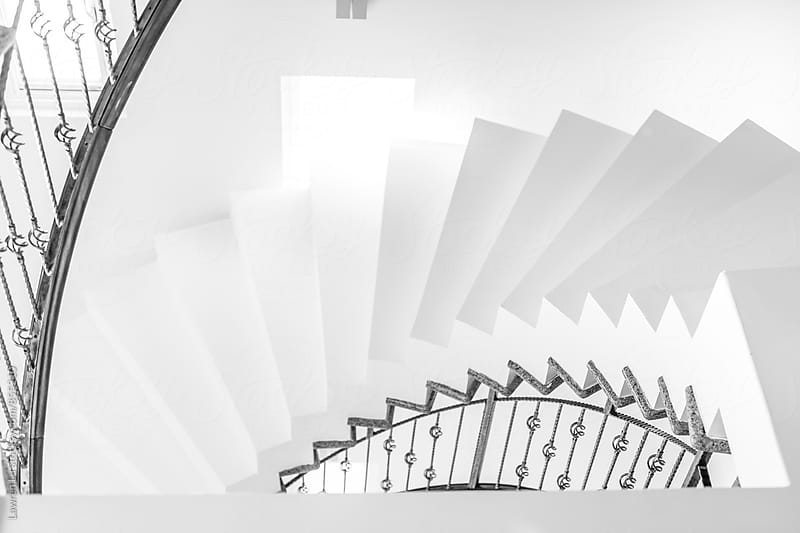 White internal spiral staircase with iron railing in building interior by Lawren Lu for Stocksy United