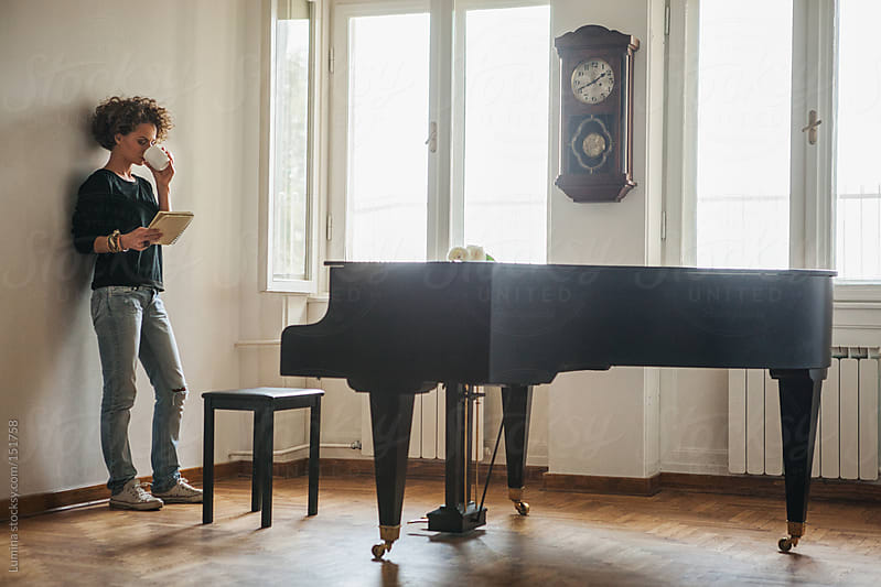 Woman Reading by the Piano by Lumina for Stocksy United
