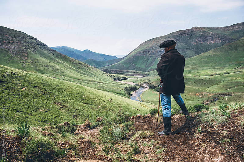 Basotho herdsman on a hill top overlooking a mountainous valley by Micky Wiswedel for Stocksy United