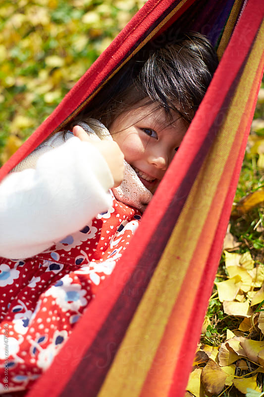 lovely little asian girl lying in the hammock outdoor in the autumn park by Bo Bo for Stocksy United