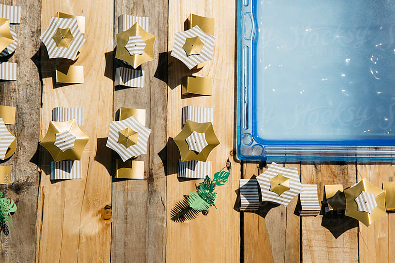 Piece of a swimming pool with Summer objects made of paper by Beatrix Boros for Stocksy United
