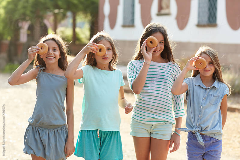 Group of young girls with a doughnut covering her eyes by Miquel Llonch for Stocksy United