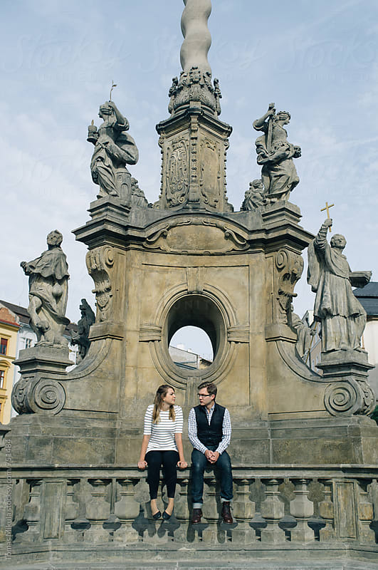 Couple is sitting on the historic railing by Tomas Mikula for Stocksy United