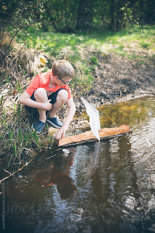 Boy holding a bark boat by a stream by Jonas Räfling for Stocksy United
