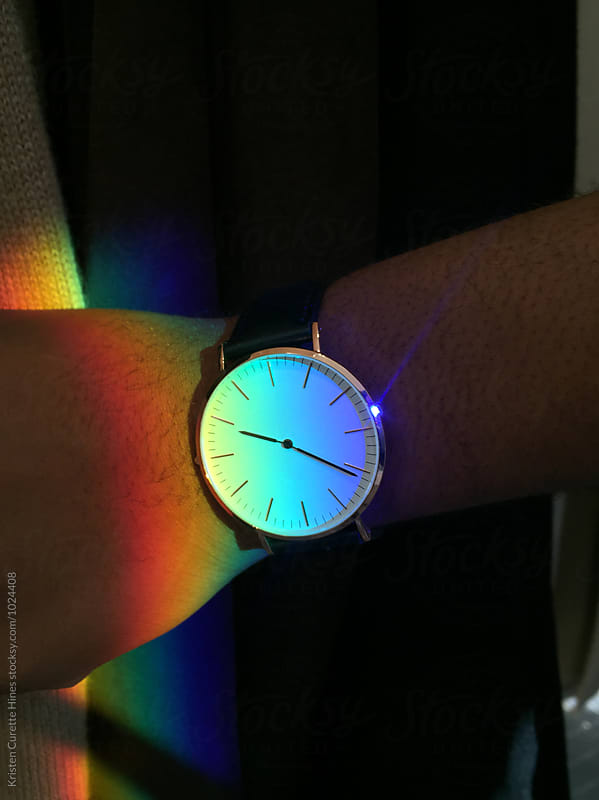 Someone wearing a watch & the sun reflecting light / rainbow on the glass by Kristen Curette Hines for Stocksy United