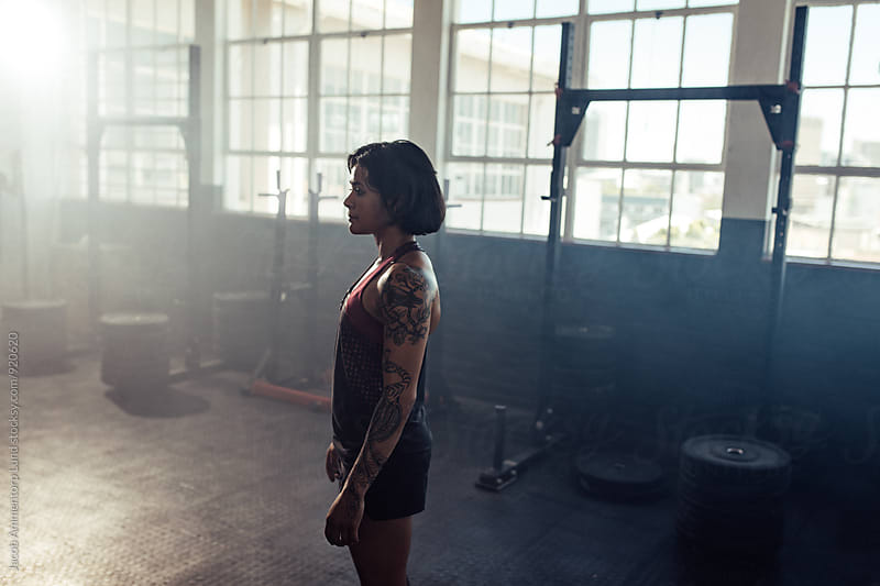 Strong tattooed woman in gym by Jacob Ammentorp Lund for Stocksy United