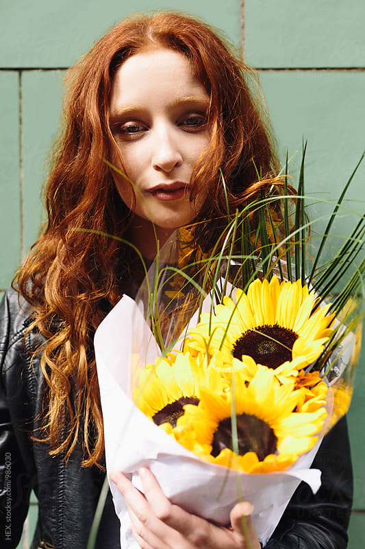 Young Redhead Woman Holding Sunflowers aginst a Wall by Mattia Pelizzari for Stocksy United