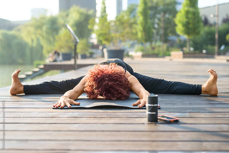 Woman meditating and stretching on a lake pontoon by RG&B Images for Stocksy United