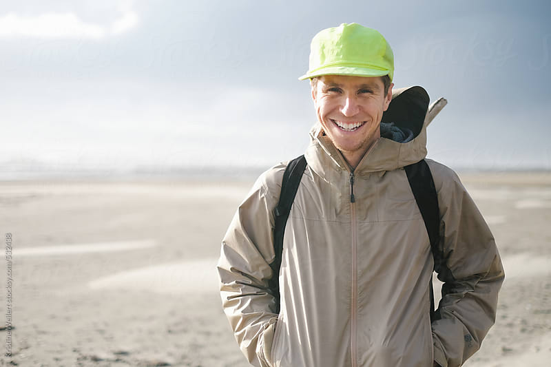 Happy smiling man on the coast by Kristine Weilert for Stocksy United