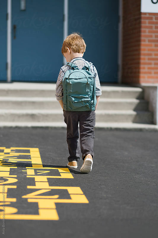 Boy with a backpack walking towards a school by Ania Boniecka for Stocksy United