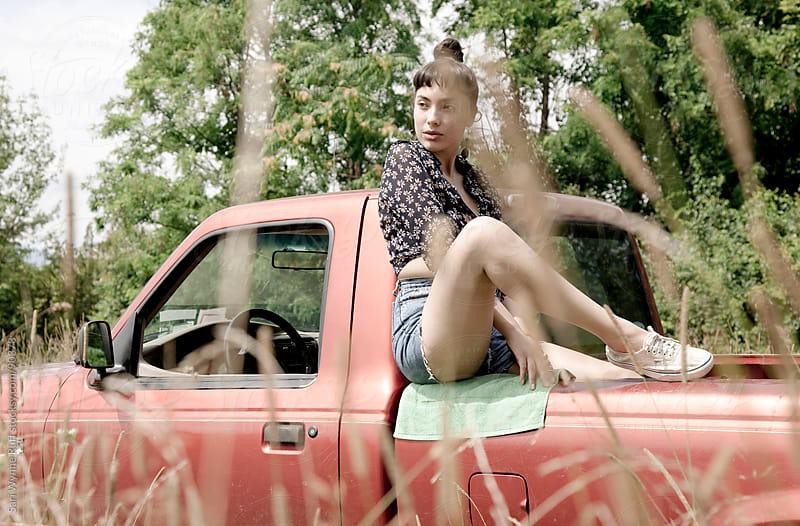 Girl sitting on back of truck by Sari Wynne Ruff for Stocksy United