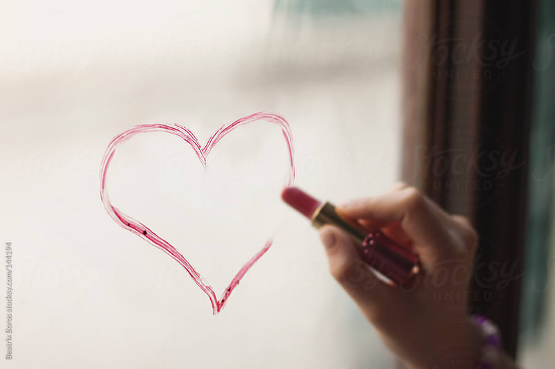 Woman drawing with lipstick a heart on the window  by Beatrix Boros for Stocksy United