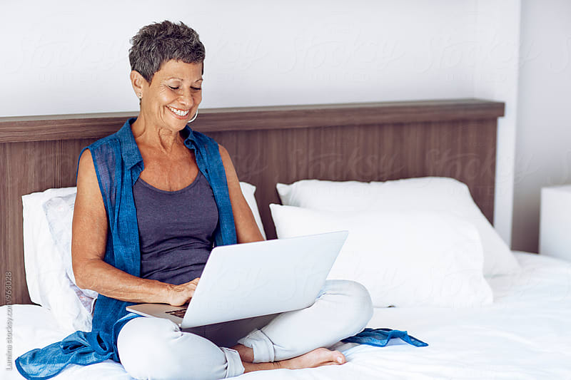 Senior Woman Uses a Laptop at Home by Lumina for Stocksy United