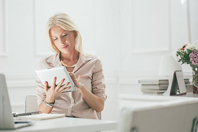 Businesswoman Using a Tablet at Her Office by Lumina for Stocksy United