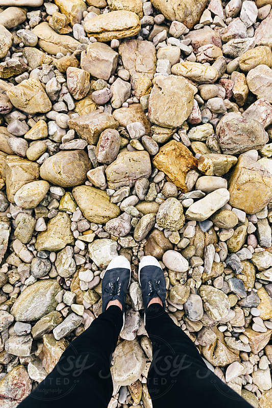 Looking down on Woman's feet standing on rocks - vertical by Jacqui Miller for Stocksy United