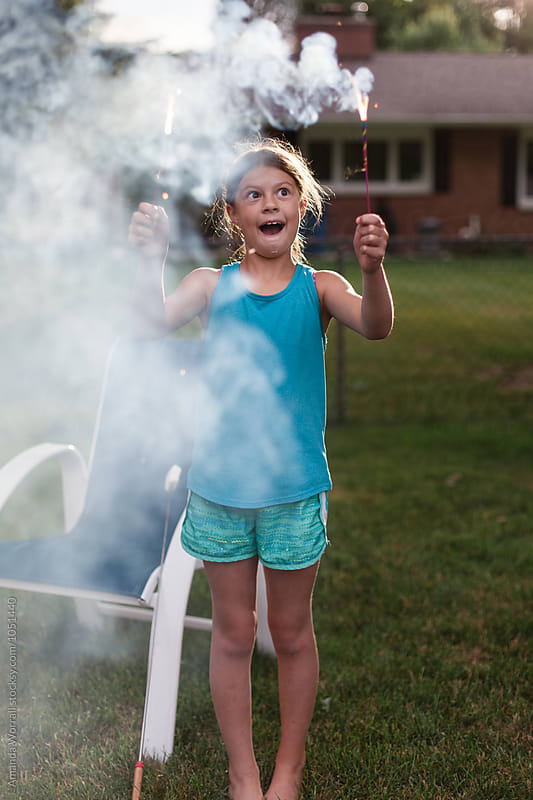 Tween girl entertained by handheld fireworks in backyard by Amanda Worrall for Stocksy United