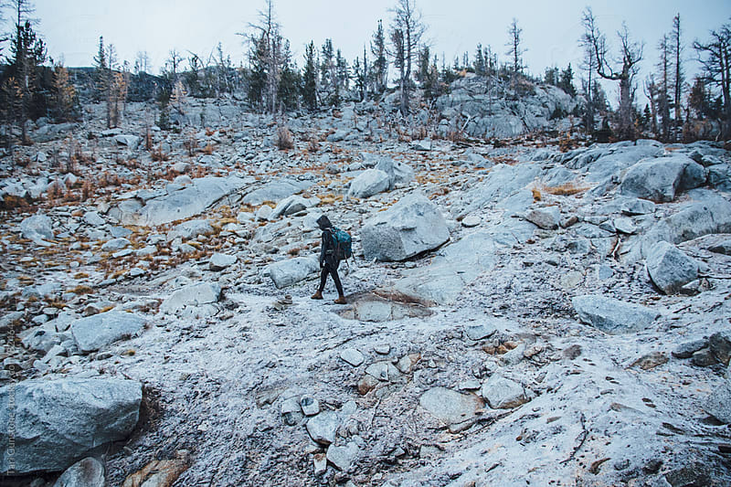 Backpacker hiking during snowfall by Tari Gunstone for Stocksy United