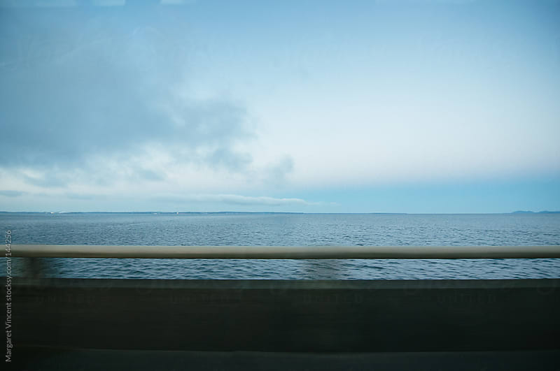 driving past a large body of water by Margaret Vincent for Stocksy United