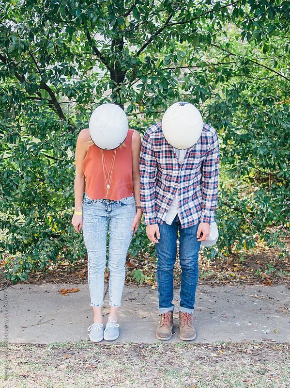 Young couple with motorcycle helmets on by Jeremy Pawlowski for Stocksy United