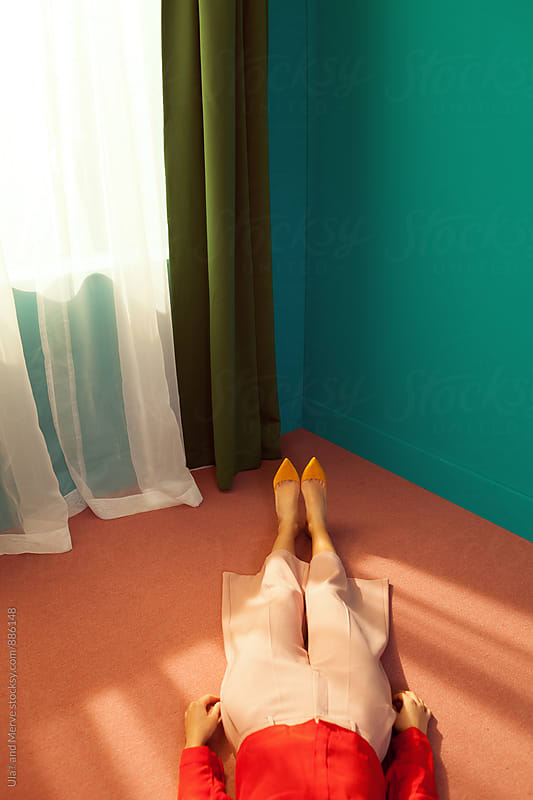 young woman lying down on the floor of the room by Ulaş and Merve for Stocksy United