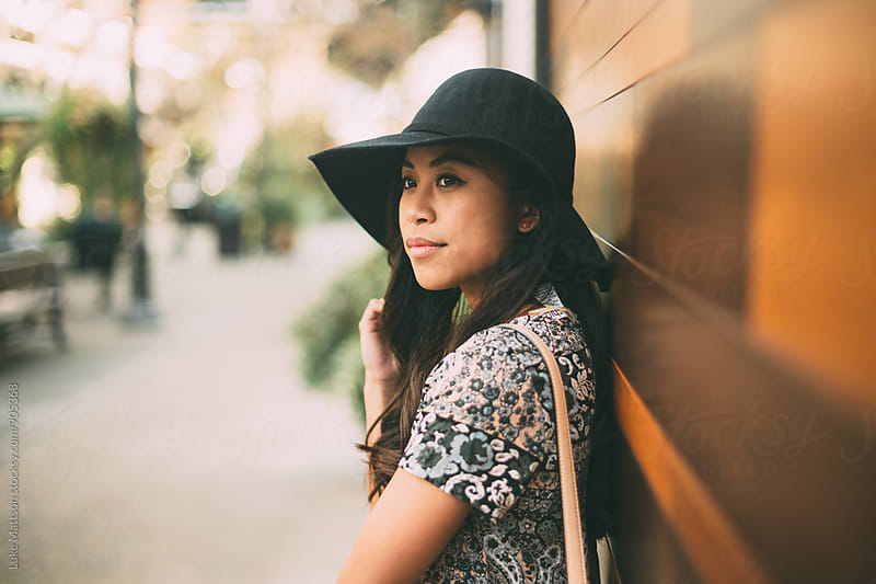 Attractive Young Woman In Sun Hat Leaning Against Wall by Luke Mattson for Stocksy United