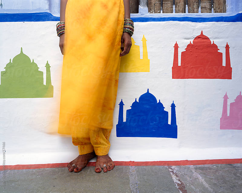 Indian woman standing infront of different coloured Taj Mahal's painted on wall. by Hugh Sitton for Stocksy United