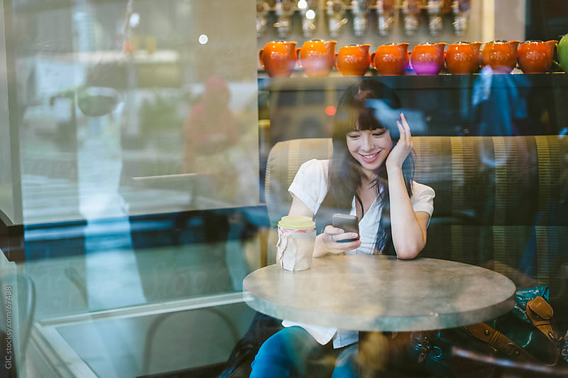 Happy woman using a phone sitting in a cafe by Simone Becchetti for Stocksy United