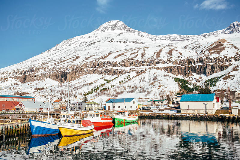 Colorful fishing boats in port in winter by Søren Egeberg Photography for Stocksy United