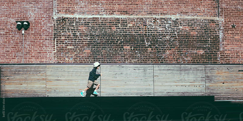 Young Boy Runs Next To Brick Wall by kelli kim for Stocksy United