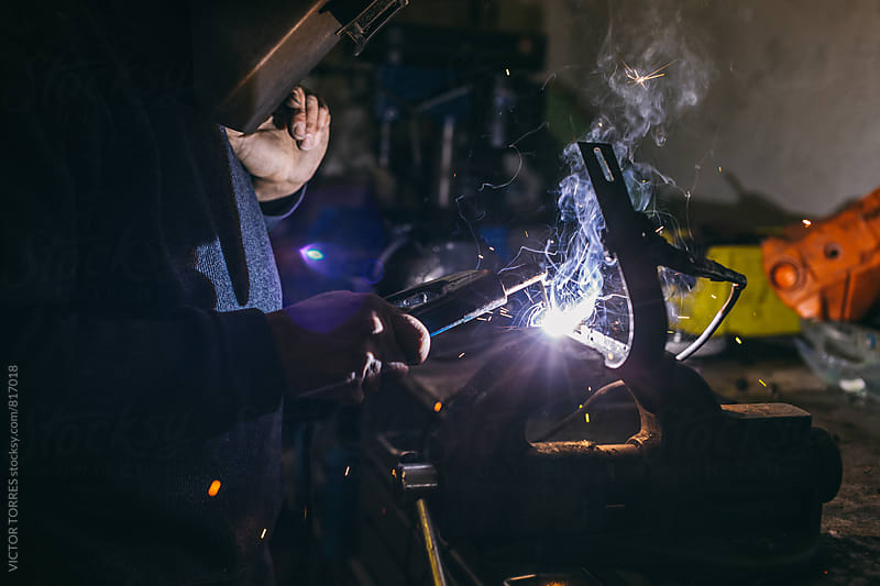 Man Welding in a Workshop by VICTOR TORRES for Stocksy United