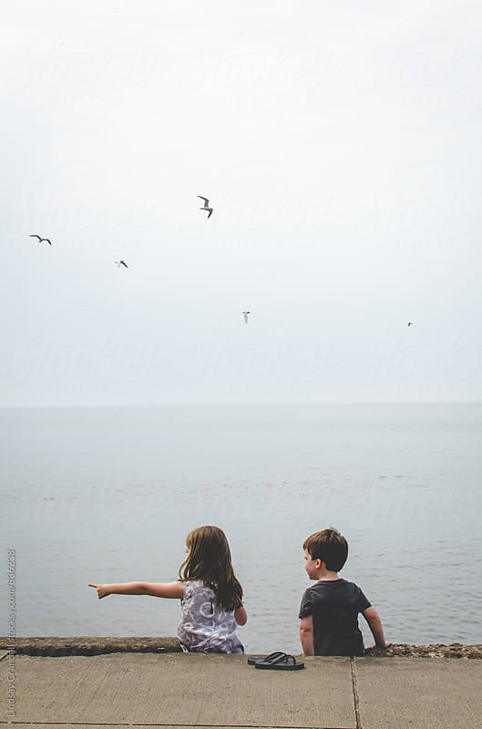 Two children sitting by the sea by Lindsay Crandall for Stocksy United