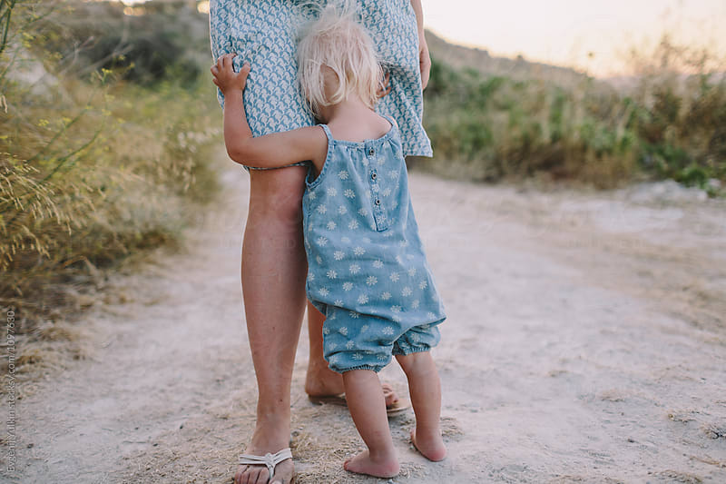 Baby girl embracing her mother legs by Evgenij Yulkin for Stocksy United