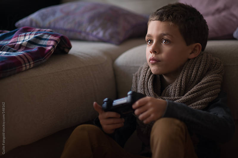 Children enjoying game console at home by Guille Faingold for Stocksy United