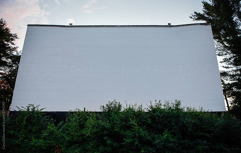 Blank screen at dusk at a drive-in movie theater by Cara Dolan for Stocksy United