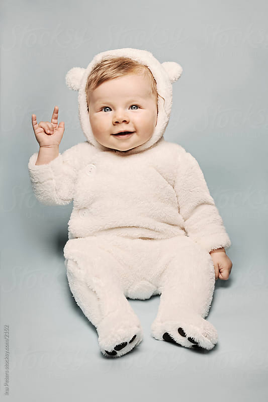 Ice Bear costumed Baby making the Devils Horn Sign by Ina Peters for Stocksy United