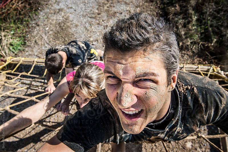 INTENSITY from a Muddy Competitor Climbing a Ropes Obstacle by Brian McEntire for Stocksy United