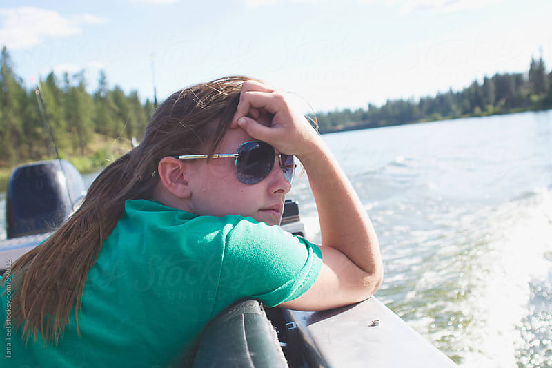 A teenager leaning on side of a moving boat by Tana Teel for Stocksy United