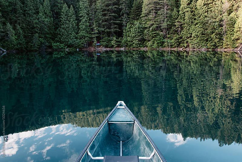 Bow of a canoe pointing toward a campsite by Justin Mullet for Stocksy United