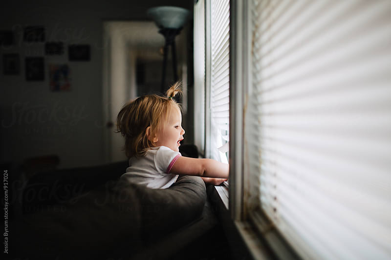 Toddler girl playing in window by Jessica Byrum for Stocksy United