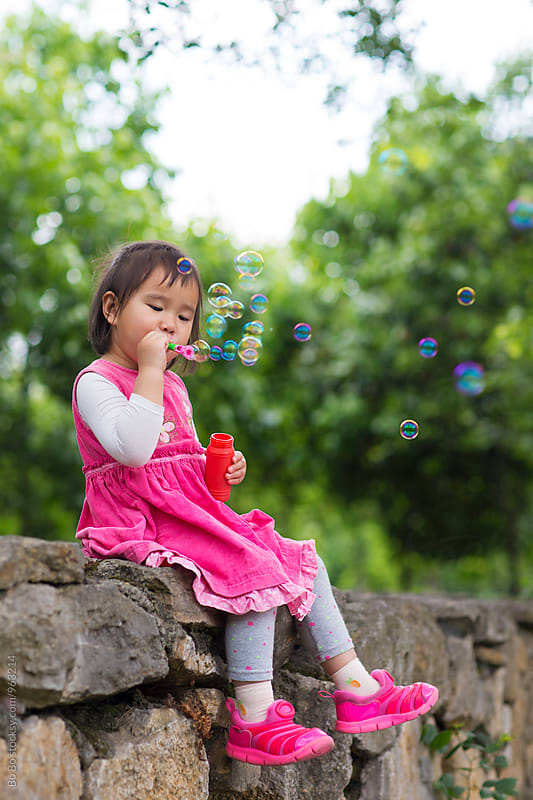 lovely girl blowing soap bubble outdoor by cuiyan Liu for Stocksy United