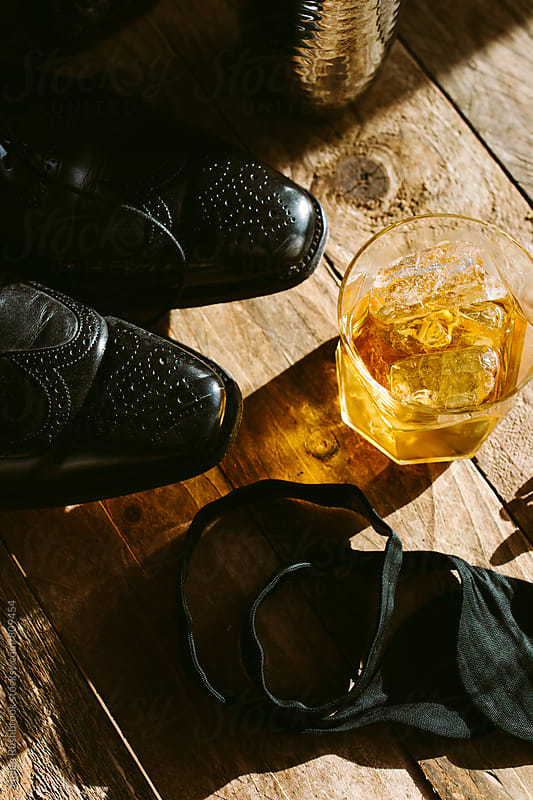 Bourbon on the rocks and a gentleman's shoes. by Helen Rushbrook for Stocksy United