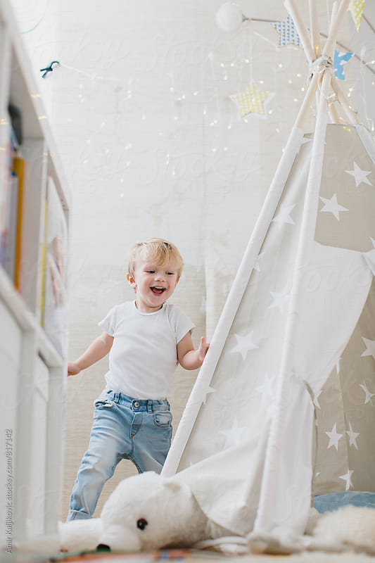 Cute little boy running in his room by Amir Kaljikovic for Stocksy United