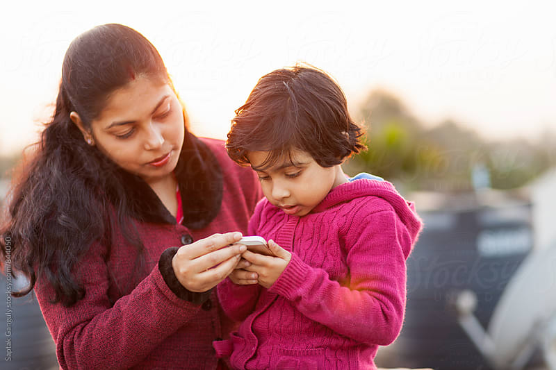 Mother and daughter browsing on mobile phone by Saptak Ganguly for Stocksy United