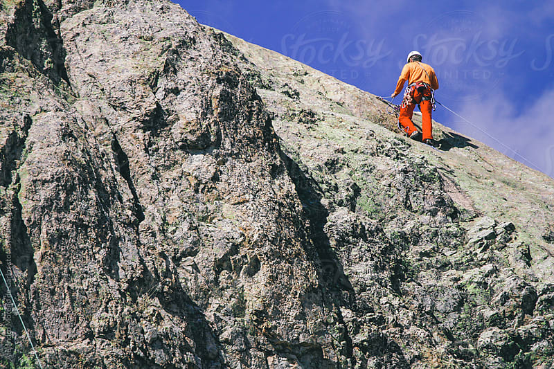 Man rappelling on a rock mountain in Spain by Alejandro Moreno de Carlos for Stocksy United